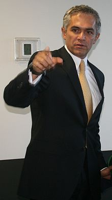 Miguel Ángel Mancera points, with his right hand, something or someone that he is looking at.