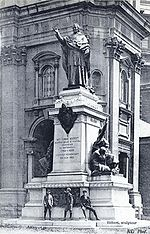 A stone statue of a robed man with hand raised, atop a plinth outside a stone building.