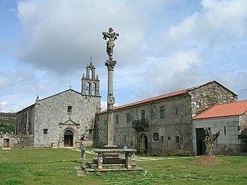 Fachada del monasterio y su iglesia, con el Cruceiro en primer plano.
