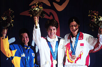 2000 Summer Olympics - Gold medallist Nancy Johnson (centre) of the U.S., raises her hands with silver medallist Cho-Hyun Kang (left), of South Korea, and bronze winner Gao Jing (right), of China, during the first medal ceremony of the 2000 Olympic Games.