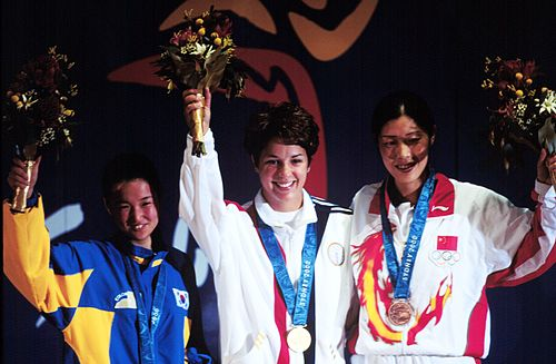Gold medallist Nancy Johnson (centre) of the U.S., raises her hands with silver medallist Cho-Hyun Kang (left), of South Korea, and bronze winner Gao Jing (right), of China, during the first medal ceremony of the 2000 Olympic Games. 2000 Olympics first medals.jpg