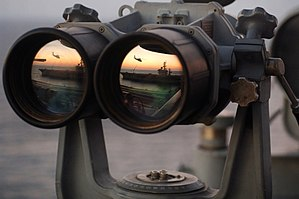 USS Dwight D Eisenhower reflected in binoculars