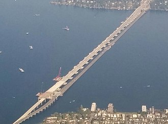 Evergreen Point Floating Bridge (2016) - New (left) and old (right) bridges in 2015 showing difference in decks: old road surface is directly on pontoons laid end-to-end, but new road surface is raised above pontoons laid perpendicular to road.