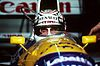 Nigel Mansell wearing a crash helmet with sponsors logos and sitting inside a blue, yellow and white racing car