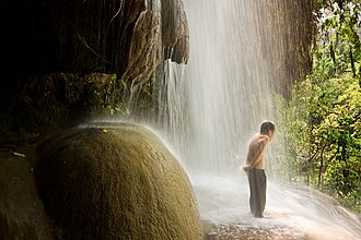 Hydrogeology - Boy under a waterfall in Phu Sang National Park, Thailand.