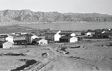 A black and while photograph of Eilat taken from the West. The settlement is small with only a few buildings. In the distance, the Jordanian settlement of Aqaba is visible, and backdropped by mountains.