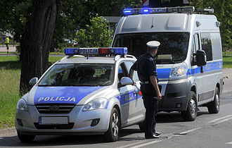 Law enforcement in Poland - A Policja officer, accompanied by two service vehicles, performs spot-checks on passing traffic