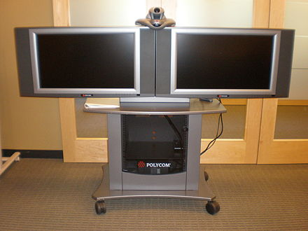 Dual display: An older Polycom VSX 7000 system and camera used for videoconferencing, with two displays for simultaneous broadcast from separate locations (2008). Polycom VSX 7000 with 2 video conferencing screens.JPG
