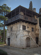A small three-storey stone house with an exterior stone staircase to the first floor, and a wooden balcony around the upper floor.
