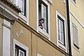 Portuguese woman watching tourists from her window (5581906128).jpg