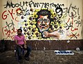 Protester opposing President Mohamed Morsi sits next to graffiti depicting Morsi on a wall in Cairo 1-Jul-2013.jpg