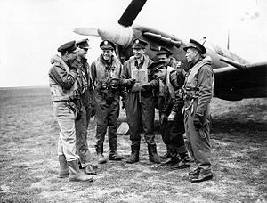 RAF Debden - Former RAF Eagle Squadron pilots, now with the USAAF 4th Fighter Group sharing a smoke in front of a Spitfire at Debden
