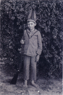 Black and white photograph of a boy dressed in a native American costume.