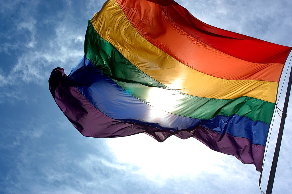 A rainbow pride flag flaps in the wind with a blue sky background and a sun spot in the center