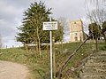 Road sign in North Stoke, Somerset, with St Martin's parish church in the background.jpg