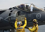 Sailor uses a tote board to communicate with the pilot of an AV-8B Harrier.A (35855356862).jpg