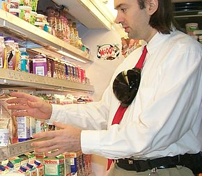 A man with a fist-sized black plastic dome attached to his tie reaches for an item on the shelf in a grocery store.