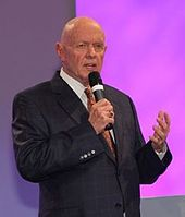 Older, bald man in a sharp suit speaking to an unseen audience