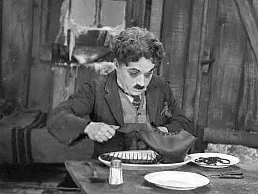 Charlie Chaplin eating a boot in his film The Gold Rush
