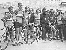 Photographie en noir et blanc d'un groupe de cyclistes se tenant debout à côté de leurs vélos à l'arrivée d'une course.