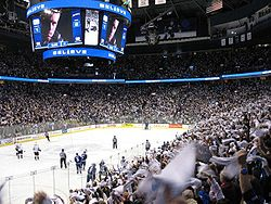 "An arena set up for ice hockey. Players skate towards center ice, while a larger crowd is waiving white towels, over head is a jumbo-tron with an extreme close-up of a player looking seriously at the camera, above and below the picture is the word ""Believe"" in white lights with a blue light background."