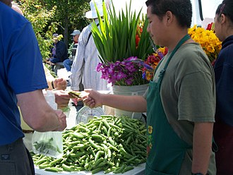 Financial transaction - Financial transaction involving money and agricultural goods at a farmers' market