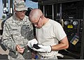 U.S. Air Force Master Sgt. Edward Braddy, with the 364th Training Squadron, coaches Airman Kyle Coates on how to swipe an aviation into-plane reimbursement card into an automated point of sale device to keep 110712-F-NS900-012.jpg