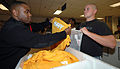 U.S. Navy recruit William Smith, right, was the first recruit to be issued the new physical training uniforms from in-processing night of arrival petty officer Culinary Specialist 1st Class Travis Thomas at 080430-N-IK959-065.jpg