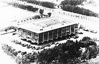 oblique, aerial image in black-and-white of a large, rectangular building
