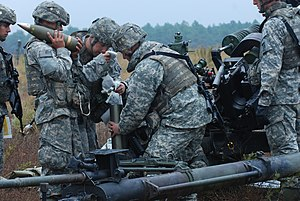 Ammunition - Preparing 105mm M119 howitzer ammunition: powder propellant, cartridge, and shell with fuze.