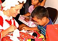 US Navy 021227-N-7813K-002 Lt. Lisa Braun of U.S. Naval Hospital Guam, hands a toy to a Chalan Pago-Ordot child displaced following Super Typhoon Pongsona during a Christmas holiday event held for the children.jpg