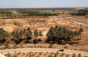 From the foot of Saddam Hussein's summer palace a Humvee is seen driving down a road towards the left. Palm trees grow near the road and the ruins of Babylon can be seen in the background.
