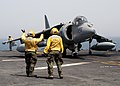 US Navy 040411-N-8053S-055 A plane director assigned to the amphibious assault ship USS Wasp (LHD 1) signals an AV-8B Harrier pilot to move forward.jpg