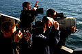 US Navy 050621-N-5549O-176 Quartermasters aboard the Nimitz-class aircraft carrier USS Ronald Reagan (CVN 76) exchange flashing light signals with USS Abraham Lincoln (CVN 72) as a Photographer's Mate takes photographs.jpg