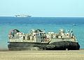 US Navy 060308-N-5067K-017 The amphibious assault ship USS Essex (LHD 2) steams off the coast of Iwo Jima as a Landing Craft Air Cushion (LCAC) lands on the beach.jpg