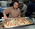 US Navy 060817-N-4856C-003 Culinary Specialist 3rd Class Elizabeth Garcia-Vargas slices pizzas for a pizza party in the ship's Flag Mess aboard the multi-purpose amphibious assault ship USS Iwo Jima (LHD 7).jpg