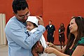 US Navy 070608-N-4047W-020 Aviation Machinist's Mate 2nd Class John Villacis greets his wife and holds his 2-month-old daughter for the first time after returning from deployment.jpg