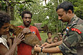 US Navy 070810-N-4954I-038 Lt. Col. Raveesh Chhajed, a veterinarian from the Indian Army, gives a rabies vaccination to a family dog during a veterinarian civil-assistance program.jpg