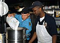 US Navy 080612-N-5283B-005 Culinary Specialist 3rd Class Andree Bode, of the German frigate FGS Bayern (F 217) pours flour into a mixing bowl while Culinary Specialist 3rd Class Jamian Pryer looks on in the galley of the guided.jpg