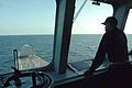 US Navy 100327-N-1876H-006 Lt. Cmdr. Adam Cheatham observes operations from the bridge of the littoral combat ship USS Independence (LCS 2).jpg