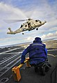 US Navy 100406-N-4774B-646 Boatswain's Mate Seaman Apprentice Anthony Orduna stands by with chock and chains to secure an SH-60F Sea Hawk helicopter.jpg