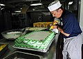 US Navy 100528-N-7949R-236 Culinary Specialist 1st Class Lamberto Vitug decorates a birthday cake for Sailors celebrating May birthdays aboard the amphibious assault ship USS Peleliu (LHA 5).jpg
