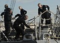 US Navy 120117-N-YF783-080 Line handlers aboard the guided-missile frigate USS Nicholas (FFG 47) pull up the mooring lines as the ship prepares to.jpg