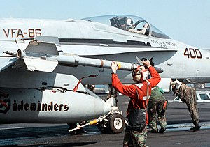 US Navy 980220-N-0507F-003 U.S. Marine Corps Lance Cpl. Leander Pickens arms an AIM-9 Sidewinder missile on a FA-18C Hornet.jpg