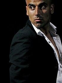 Umar Khan posing in a black suit.jpg
