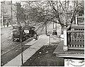 Unidentified sidewalk scene with balconies, parked automobiles, and pedestrians.jpg