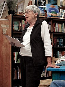 Photograph of Ursula K. Le Guin standing and reading aloud in a bookshop