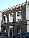 foto van Pand (thans niet gepleisterd), met verdieping en mezzanino onder flauwhellend, met pannen gedekt zadeldak