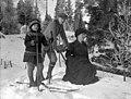 Vinterbild. Gruppfoto av en kvinna som sitter på en sparkstötting och en pojke och en flicka på skidor - Nordiska Museet - NMA.0057526.jpg