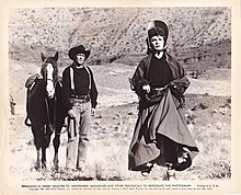Printer poster with a photograph and text underneath. A man is standing holding the reins of his horse. A woman is running towards the camera. They are in a dry landscape with a stony canyon wall in the background. The text consists of a copyright notice and a license for periodicals to reproduce the photograph.